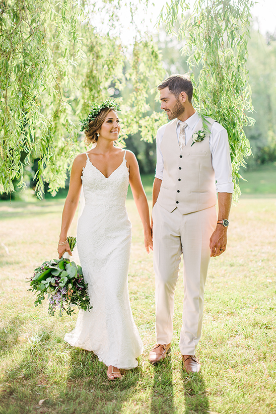 Bride and groom walking through nicely lit willow trees